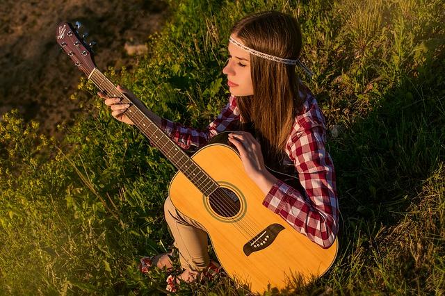 dívka v trávě s kytarou