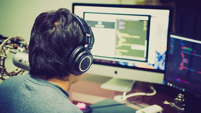 muž se sluchátky u počítače