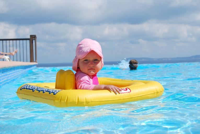 malá holčička v dětském plovacím kruhu se koupe v bazénu
