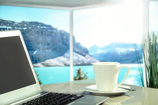 na stole notebook, hrneček a výhled za oknem na vodu a hory