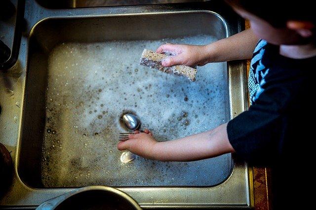 dítě pomáhá v kuchyni mýt nádobí